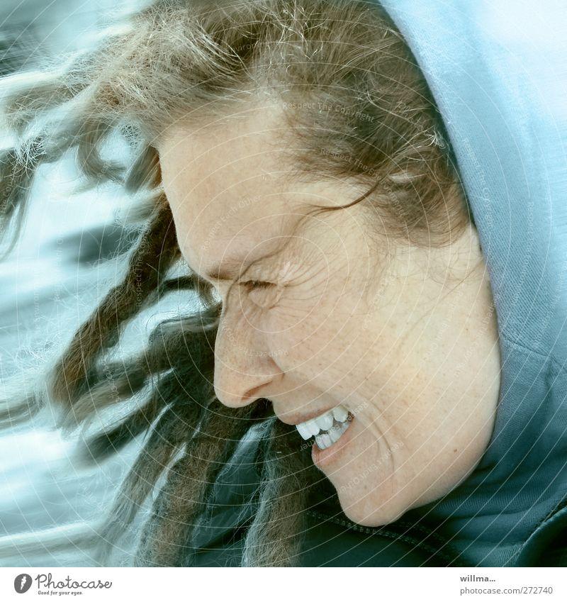 fröhliche Frau mit Rastalocken und Kapuze bei stürmischem Wnd Junge Frau Jugendliche Gesicht Erwachsene Wind Sturm Kapuzenpullover lachen authentisch Glück