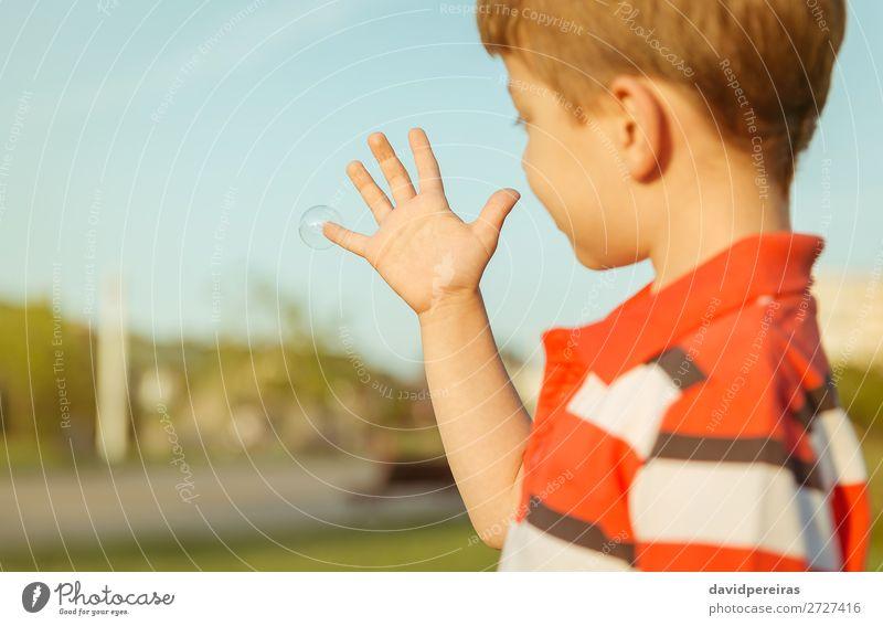 Süßer Junge sieht aus wie eine Seifenblase in seiner offenen Hand. Lifestyle Freude Glück schön Leben Erholung Freizeit & Hobby Spielen Freiheit Sommer Garten