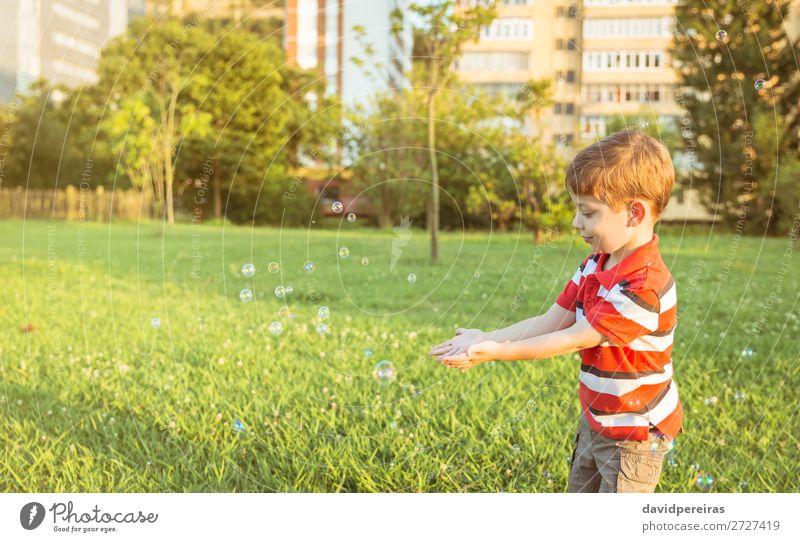 Glücklicher Junge spielt mit Seifenblasen im Park. Lifestyle Freude schön Leben Erholung Freizeit & Hobby Spielen Freiheit Sommer Garten Kind Mensch Mann