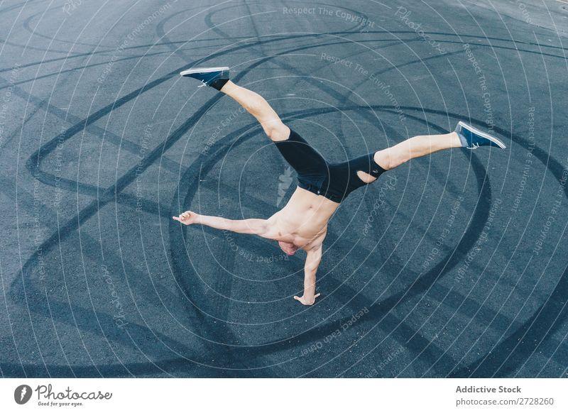 Anonymer Mann, der auf dem Bürgersteig tanzt. Tänzer Gleichgewicht Straßenbelag Handstand Breakdancer akrobatisch sportlich