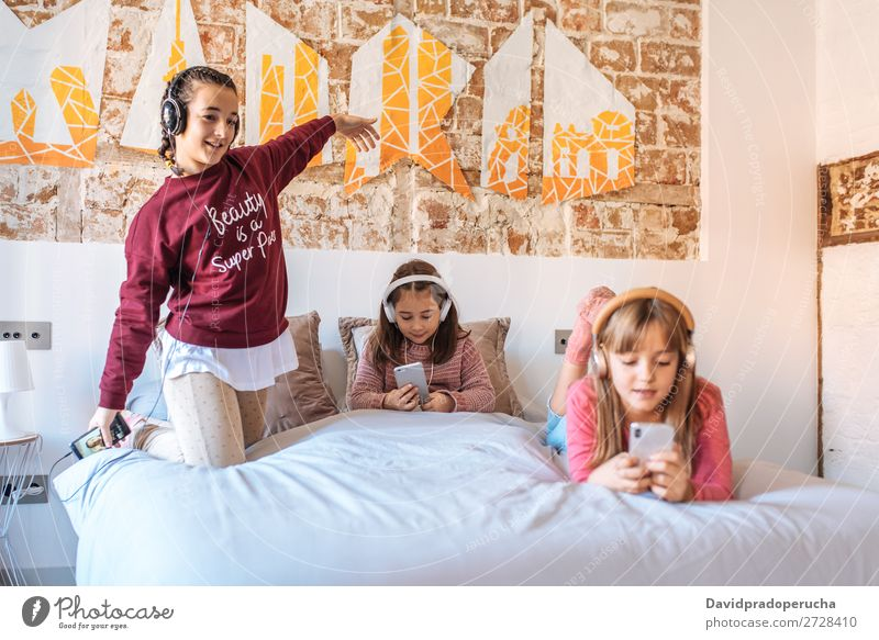 Drei Schwestern spielen miteinander und liegen zu Hause im Bett und hören Musik. Schlafzimmer Mädchen Glück Familie & Verwandtschaft weiß gemütlich Jugendliche