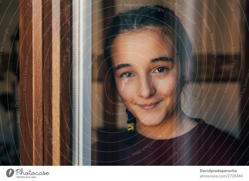 Porträt eines jungen Teenagermädchens, das durch das Fenster schaut. Mädchen Jugendliche Kind vereinzelt Einsamkeit