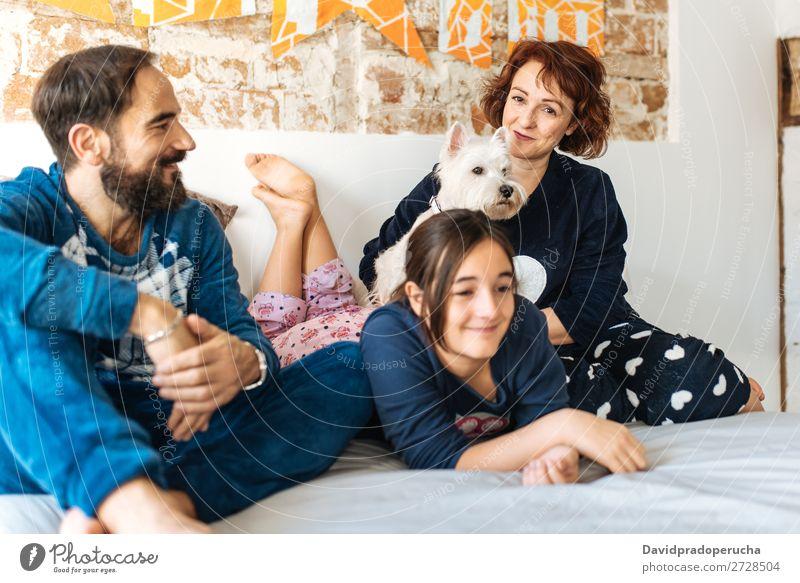 Ein Paar entspannt zu Hause im Bett mit seiner kleinen Tochter und dem Hund. Zuneigung Schlafzimmer Ehefrau Ehemann Kind Haustier Welpe Mama Papa Eltern Vater