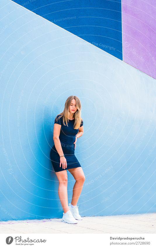 Glückliche, schöne junge Frau, die an einer bunten Wand posiert. mehrfarbig blond Lächeln Mode Model rot