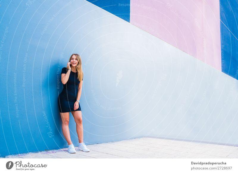 Glückliche junge Frau auf dem Handy an einer bunten Wand mehrfarbig blond Telefon Mobile Technik & Technologie Kleid