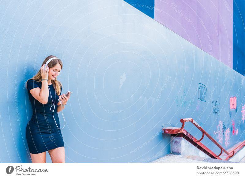 Glückliche junge Frau, die Musik auf dem Handy an einer bunten Wand hört. blond mehrfarbig hören Telefon Mobile