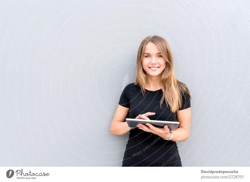 Glückliche junge Frau auf dem Tablett an der Wand vereinzelt blond Tablet Computer Technik & Technologie Kaffee Jugendliche schwarz