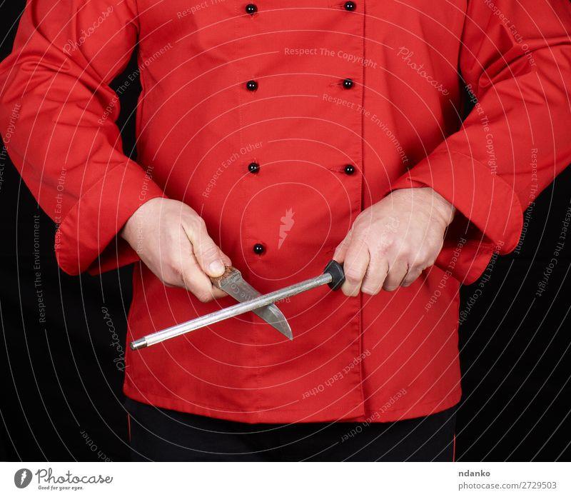 Koch in roter Uniform schärft ein Messer Küche Restaurant Beruf Mensch Mann Erwachsene Hand Stahl stehen schwarz Klinge Kaukasier Küchenchef zerkleinernd