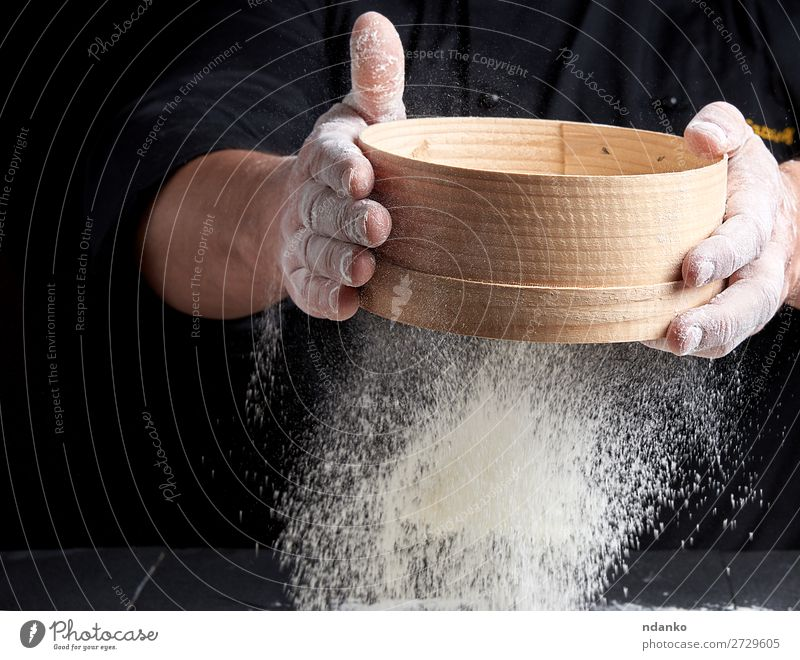 Mann siebt weißes Weizenmehl Teigwaren Backwaren Brot Ernährung Tisch Küche Koch Mensch Erwachsene Hand Sieb Holz Bewegung machen frisch schwarz backen Bäcker