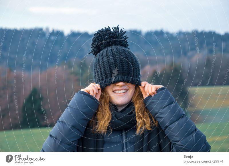 Jungesl ächendes Mädchen mit einer blauen Mütze über dem Gesicht Lifestyle Freude Glück Ausflug Winter wandern feminin Junge Frau Jugendliche 1 Mensch