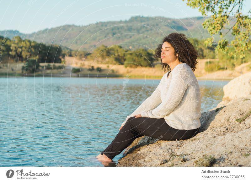 Frau ruht sich am See aus sitzen Küste ruhen Augen geschlossen Stein Felsen Natur Wasser Jugendliche Sommer Mensch Landschaft Einsamkeit