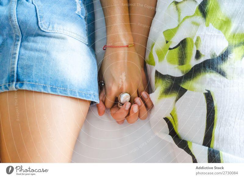 Zuschneiden eines weiblichen Paares, das Händchen hält. Frau Homosexualität Glück Liebe lügen Bett Händchenhalten Freundin Partnerschaft Mensch schön