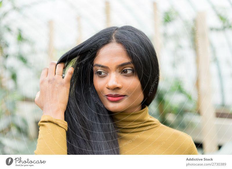 Hübsche indische ethnische Frau im Treibhaus Gewächshaus Natur grün Stil Blick in die Kamera