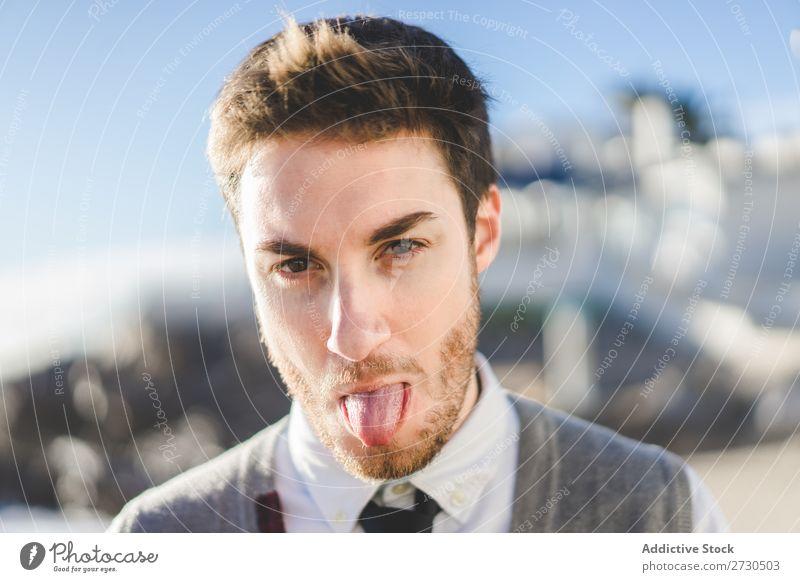 Mann zeigt Zunge im Sonnenlicht ausspannen spielerisch Menschliches Gesicht Porträt Grimasse Fröhlichkeit Zunge zeigen Aufregung Spielen Ausdruck konfrontierend