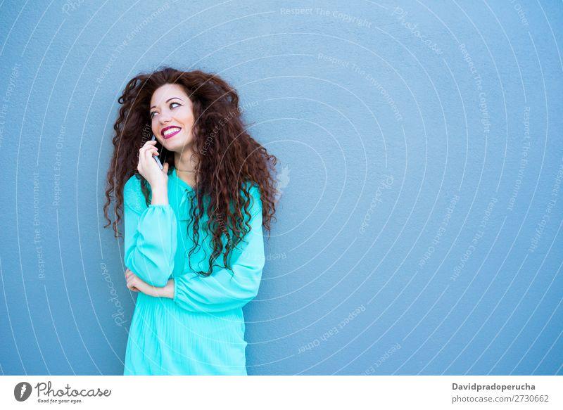 Glückliche junge Frau auf dem Handy an einer bunten Wand rothaarig Telefon Business Geschäftsfrau Technik & Technologie Mobile Lächeln