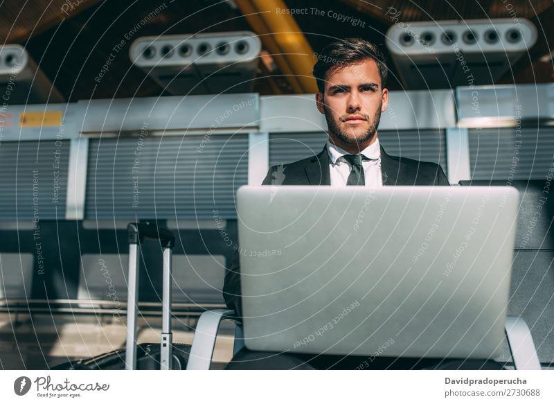 Junger Geschäftsmann sitzt am Computer mit dem Koffer am Flughafen und wartet auf den Flug. Mann Ferien & Urlaub & Reisen Notebook WiFi Technik & Technologie