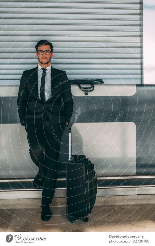 Junger Geschäftsmann steht mit dem Koffer am Flughafen und wartet auf den Flug. Mann Ferien & Urlaub & Reisen Business warten Flugzeug Tor im Ausland Gebäude