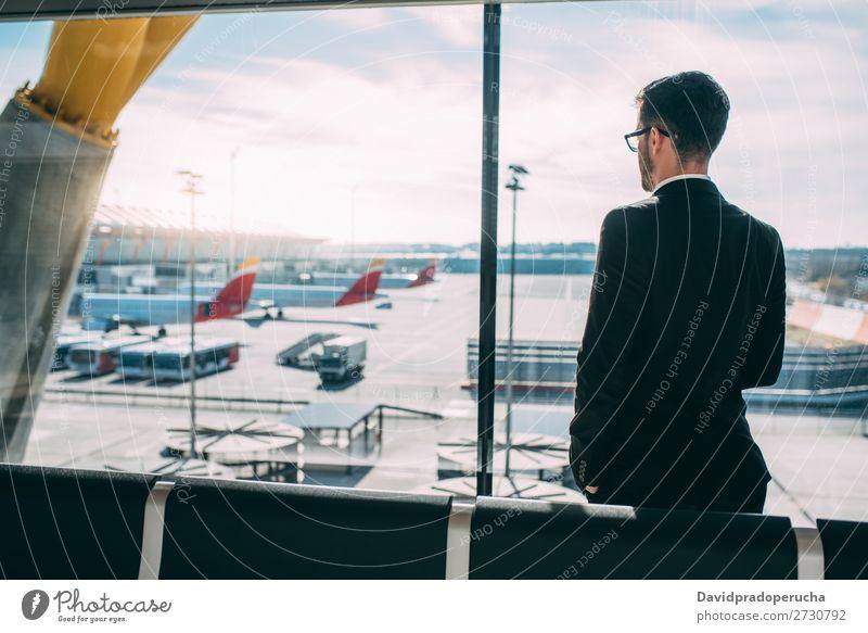 Zurück von einem jungen Geschäftsmann, der mit dem Koffer am Flughafen steht und auf den Flug wartet. Mann Ferien & Urlaub & Reisen Schatten Rücken Business