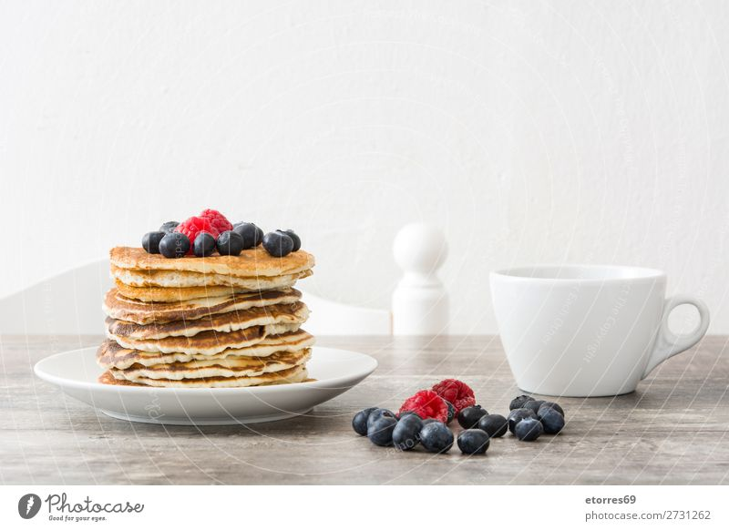 Pfannkuchen mit Himbeeren und Heidelbeeren auf Holztisch Süßwaren Dessert Frühstück Blaubeeren Beeren blau rot backen Lebensmittel Gesunde Ernährung