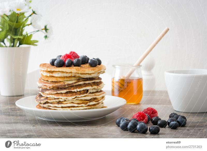 Honig in Pfannkuchen mit Himbeeren und Blaubeeren gießen. Bonbon Dessert Frühstück Beeren blau rot backen Lebensmittel Gesunde Ernährung Foodfotografie Speise
