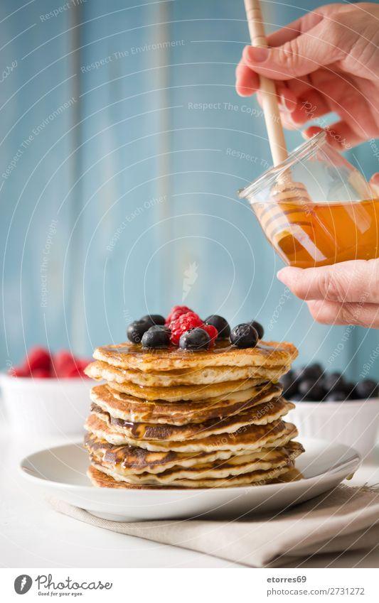 Honig in Pfannkuchen mit Himbeeren und Blaubeeren gießen. Liebling Süßwaren Dessert Frühstück Beeren blau rot backen Lebensmittel Gesunde Ernährung