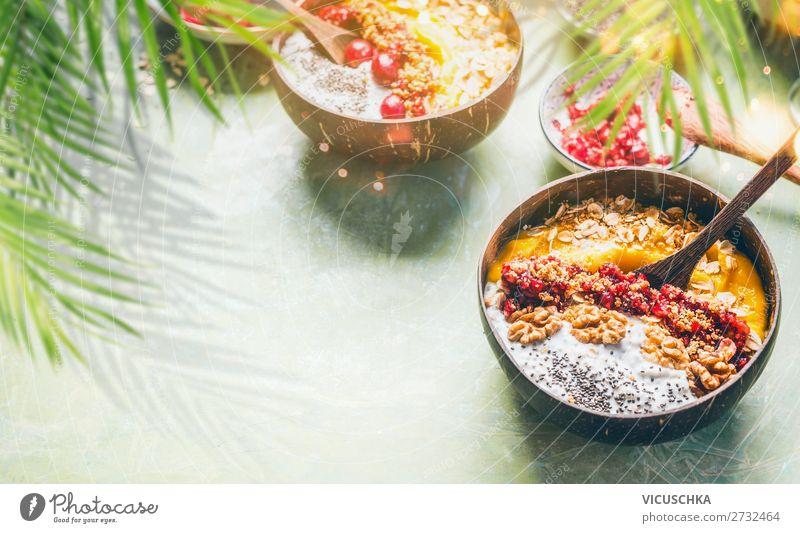 Smoothie-Mangoschale mit Chiasamen-Joghurtpudding und Preiselbeeren, Nüssen, Haferflocken-Topping in Kokosnussschalen mit Löffel. Gesunde, saubere Frühstücksnahrung. Kopierraum für Ihren Text oder Ihr Design