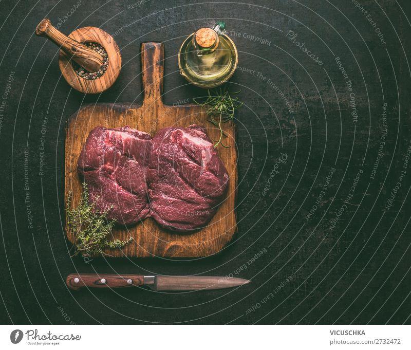 Rohes Marmor-Rindfleisch auf Holzschneidebrett mit Kräutern, Gewürzen, Öl und Messer auf dunklem, rustikalem Hintergrund, Draufsicht. Kopierfeld für Ihr Design oder Kochrezepte