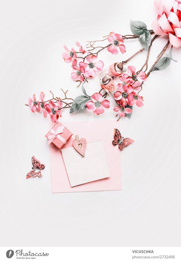 Schönes Grußkartenmock Up mit Blumen, Band, kleiner Geschenkbox und Herzen in Korallenfarbe auf weißem Hintergrund, Ansicht von oben. Flach gelegt. Abstraktes Liebes- und Ferienkonzept. Blog-Layout