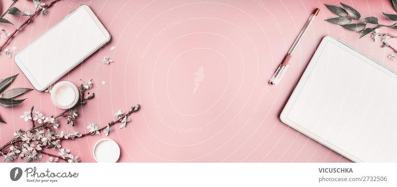 Smartphone und Tablet-PC auf pastellrosa Desktop-Hintergrund mit Kosmetik, Schreibwarengeschirr und weißen Blütenzweigen, Ansicht von oben. Beaut-Blog und weibliches Geschäftskonzept. Flachlegung, Banner