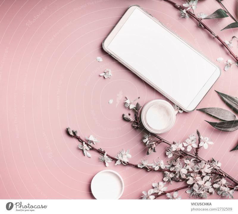 Smartphone-Attrappe auf pastellrosa Desktop mit Kosmetik und Blumen, Ansicht von oben. Schönheitsblog und weibliches Geschäftskonzept Pastell Hintergrund Blüte