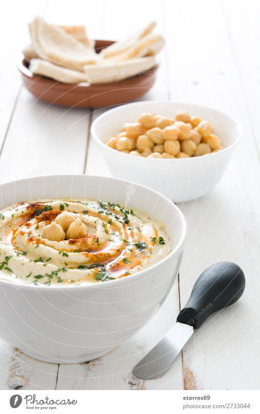 Hummus in der Schüssel und Pita-Brot auf Holztisch. Lebensmittel Gesunde Ernährung Foodfotografie Speise Kichererbsen Koriander Zitrone Olivenöl