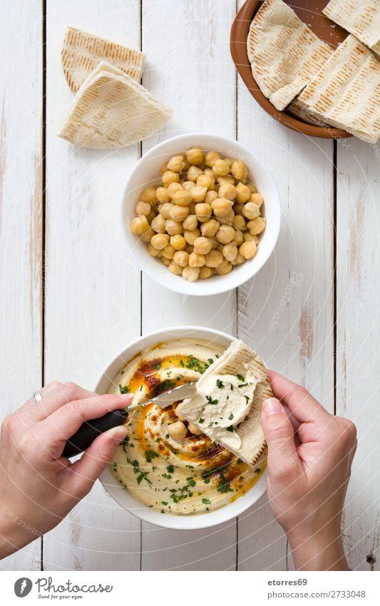 Frau beim Eintauchen von Hummus mit Fladenbrot auf weißem Holztisch Pita Brot Lebensmittel Gesunde Ernährung Foodfotografie Kichererbsen Koriander Zitrone