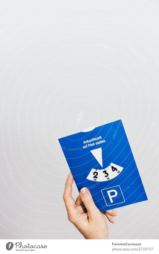 A woman's hand holding a parking meter Mensch blau weiß Hand feminin Verkehr 3 Stress Personenverkehr Autofahren Parkplatz parken Parkuhr Parkplatzsuche