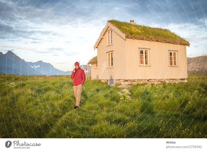 Junger Mann vor norwegischer Hütte in Mitternachtssonne Ferien & Urlaub & Reisen Abenteuer Ferne Sommerurlaub Berge u. Gebirge Jugendliche Gras Norwegen
