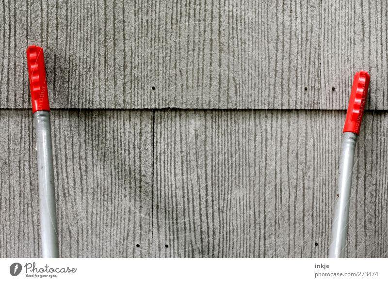 Zusammen ist man weniger allein rot Haus Wand grau Mauer Fassade trist Griff Gartenarbeit Plattenbau anlehnen Schubkarre Silikat-Mineral
