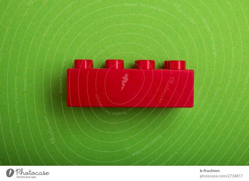 roter Baustein auf grünem Hintergrund Freude Spielen Haus Hausbau Renovieren Spielzeug Kunststoff wählen gebrauchen beobachten machen Spielstein 1 bauen einzeln