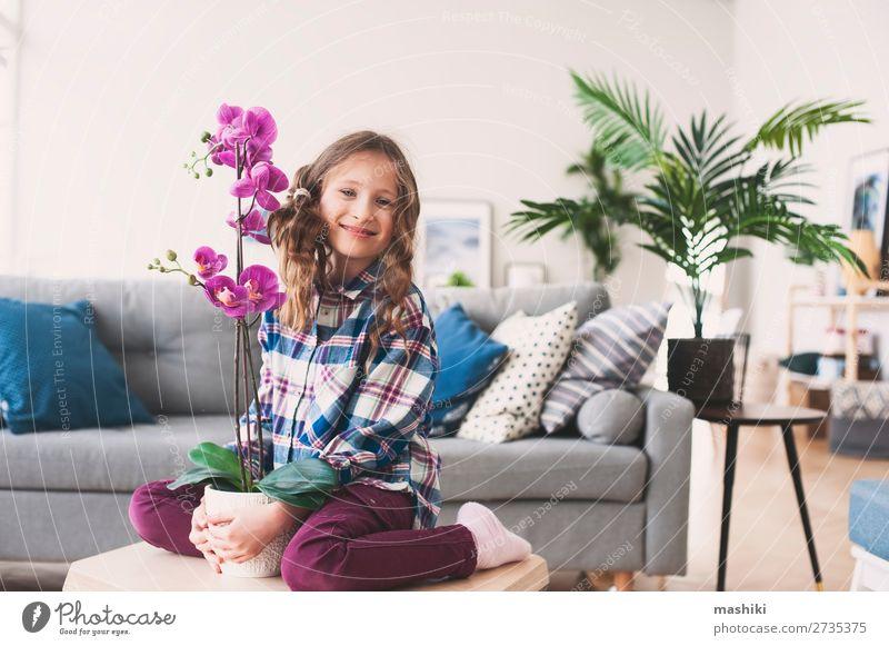 glückliches Kind posiert mit Orchideenblume Topf Lifestyle exotisch schön Wohnung Wohnzimmer Gartenarbeit Pflanze Blume Blatt Wachstum klein modern neu rosa