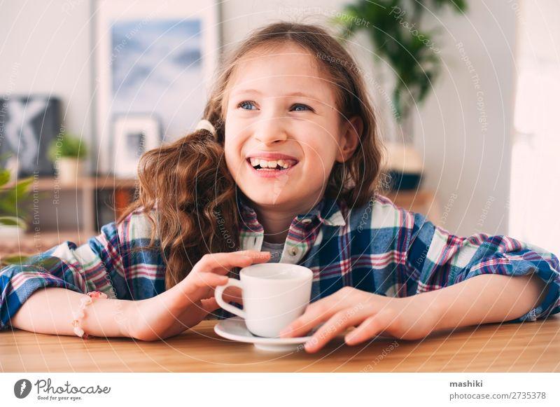 glückliches Kind Mädchen trinkt Tee zum Frühstück. Kakao Lifestyle Glück Erholung Spielen Küche Kindererziehung Mensch Kindheit Wärme genießen heiß lustig