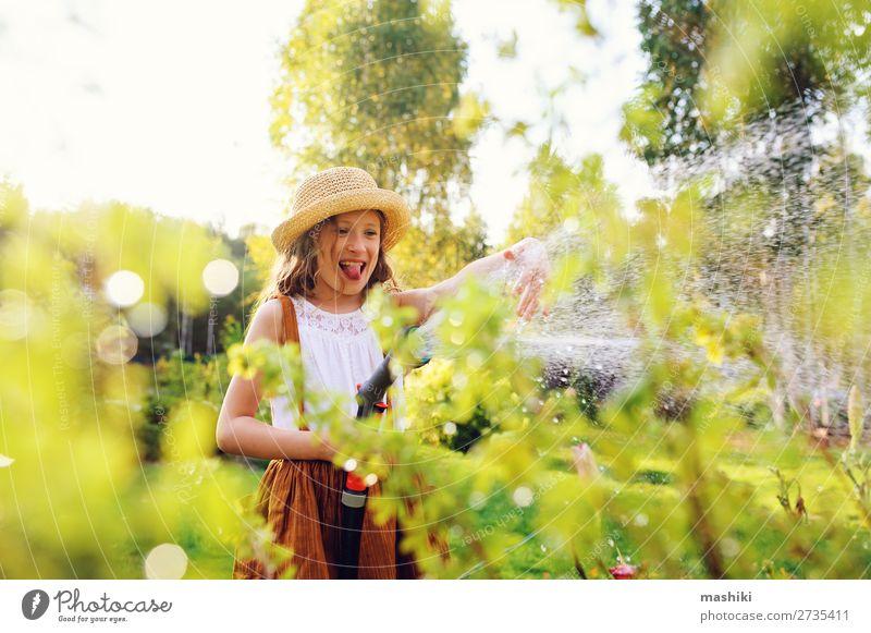 fröhliches Kind Mädchen Blumen gießen mit Schlauch im Sommergarten Lifestyle Freizeit & Hobby Garten Gartenarbeit Natur Landschaft Pflanze Frühling Lächeln