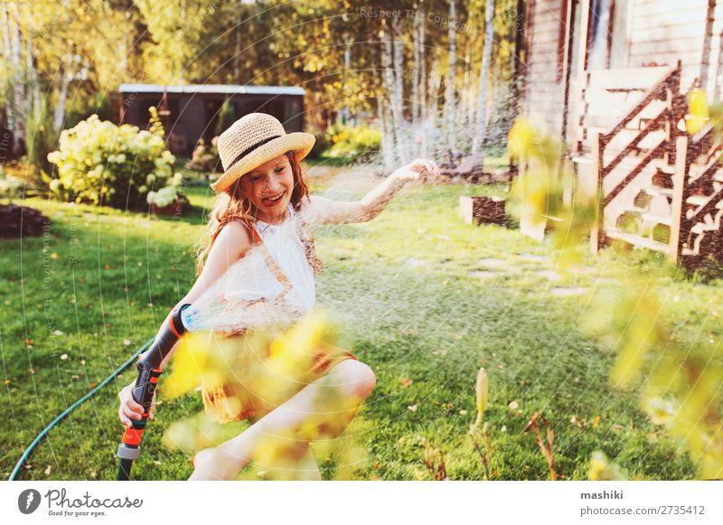 fröhliches Kind Mädchen Blumen gießen mit Schlauch im Sommer Lifestyle Freude Freizeit & Hobby Spielen Garten Arbeit & Erwerbstätigkeit Gartenarbeit Natur