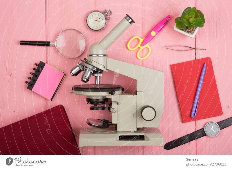 Bildungskonzept - Notizblock, Mikroskop auf dem rosa Holztisch Schreibtisch Tisch Wissenschaften Schule lernen Klassenraum Tafel Studium Labor Buch Bibliothek