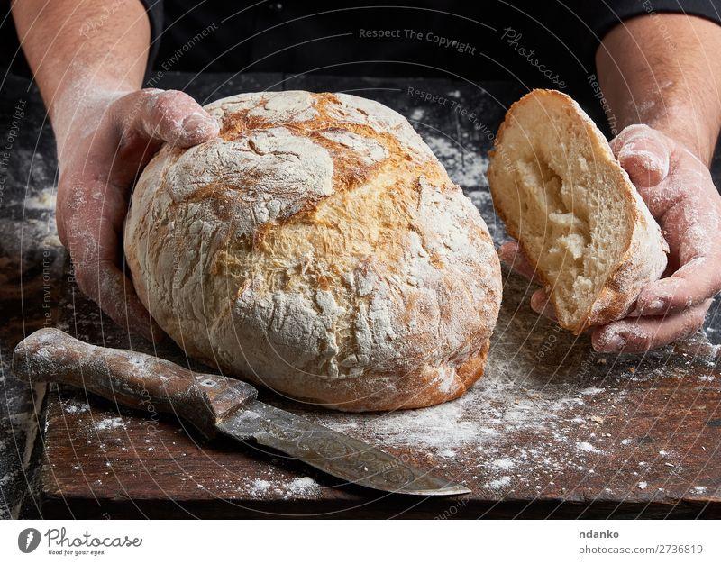 Koch in einer schwarzen Tunika hält frisch gebackenes Brot bereit. Ernährung Tisch Küche Mensch Hand Finger Holz Essen machen dunkel braun weiß Tradition Bäcker