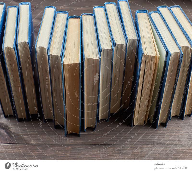 Stapel von Büchern in einem blauen Umschlag lesen Tisch Wissenschaften Schule Studium Menschengruppe Buch Bibliothek Papier Sammlung Holz lernen braun gelb
