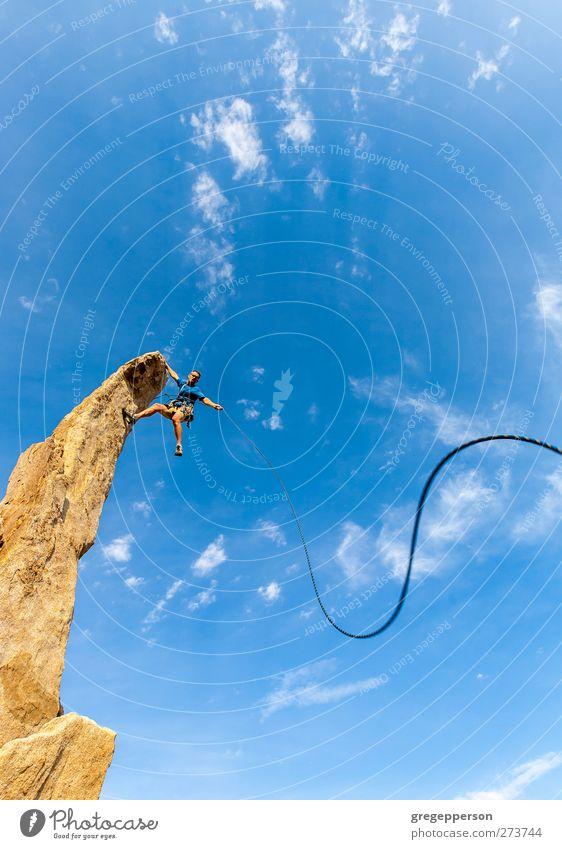 Der Kletterer baumelt vom Gipfel. Leben Abenteuer Klettern Bergsteigen Erfolg Seil maskulin Mann Erwachsene 1 Mensch Felsen hängen blau selbstbewußt Kraft
