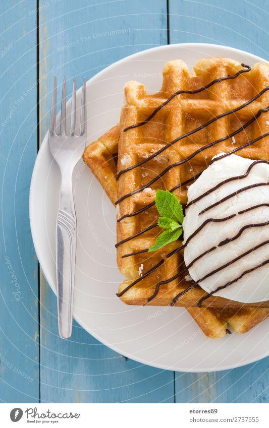Belgische Waffeln mit Eis auf blauem Holztisch. Dessert Speiseeis Belgier Belgien weiß süß Lebensmittel Gesunde Ernährung Foodfotografie Hintergrund neutral