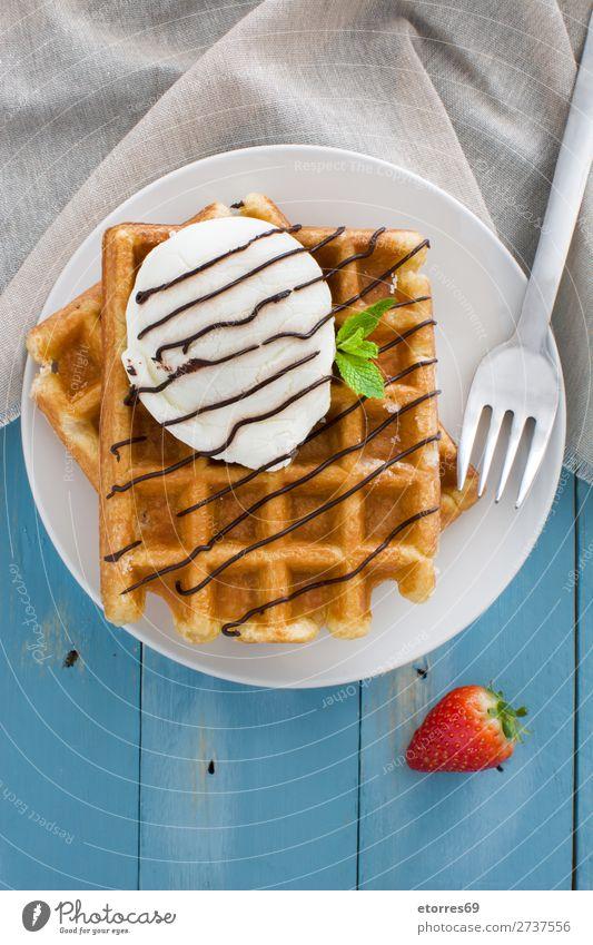 Belgische Waffeln mit Eis auf blauem Holztisch Dessert Speiseeis Belgier Belgien weiß süß Lebensmittel Hintergrund Frühstück Wafer Minze Sirup Haufen Erdbeeren