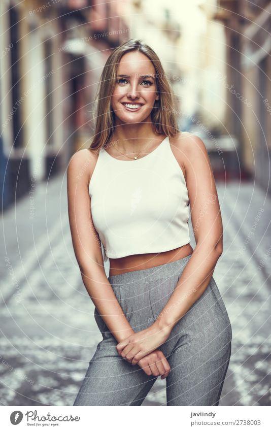 Schöne junge blonde Frau, die im urbanen Hintergrund lächelt. Lifestyle elegant Stil Glück schön Haare & Frisuren Sommer Mensch feminin Junge Frau Jugendliche