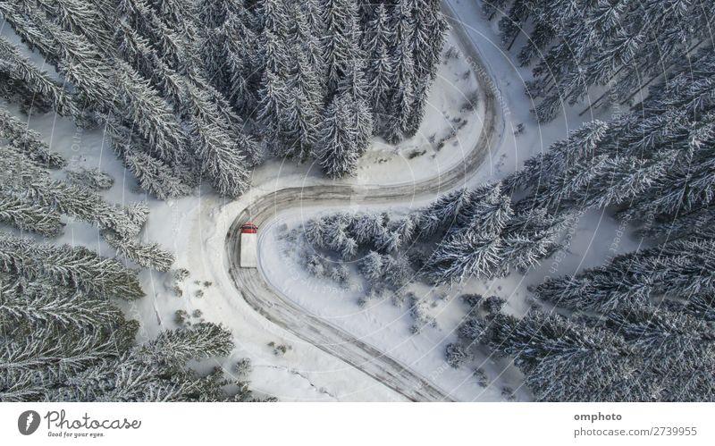 Luftlandschaft mit mäandrierender verschneiter winterlicher Bergstraße mit einem fahrenden Lastwagen Winter Schnee Berge u. Gebirge Natur Landschaft Baum Wald