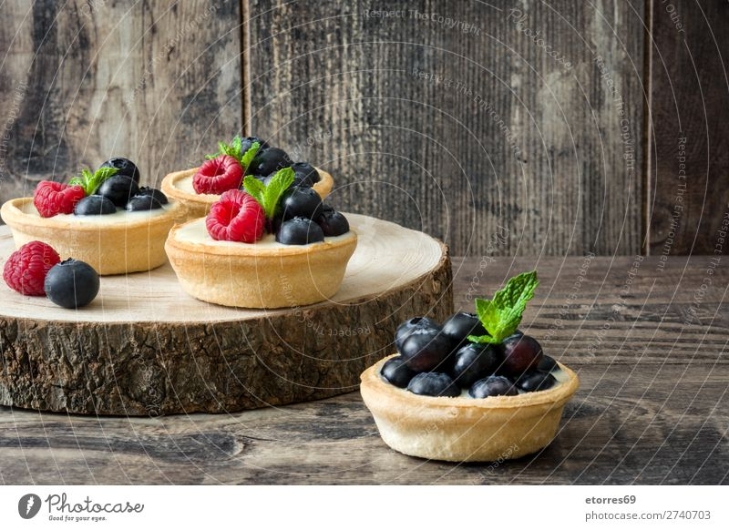 Köstliche Törtchen mit Himbeeren und Heidelbeeren auf dem Stamm Teilchen Blaubeeren Frucht Dessert Lebensmittel Gesunde Ernährung Foodfotografie lecker Sahne