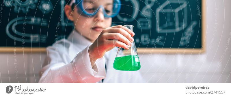 Ernsthafter Junge hält Flasche mit chemischer Flüssigkeit Spielen Tisch Wissenschaften Kind Klassenraum Tafel Labor Internet Mensch Kindheit authentisch Neugier